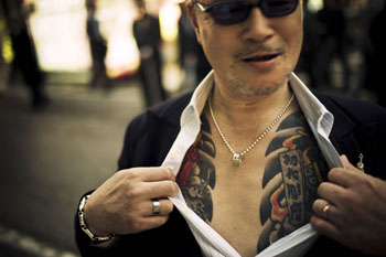 A yakuza street fighter shows off his tattoo. © ANTON KUSTERS, 2011